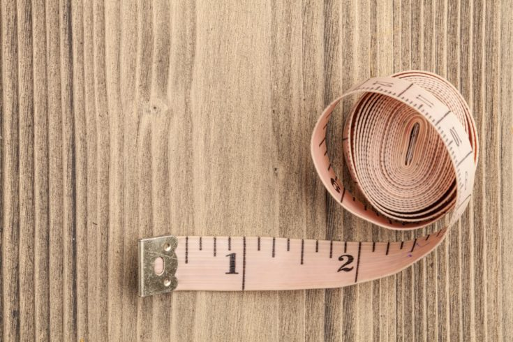 Tape measure on old wooden background. Top view