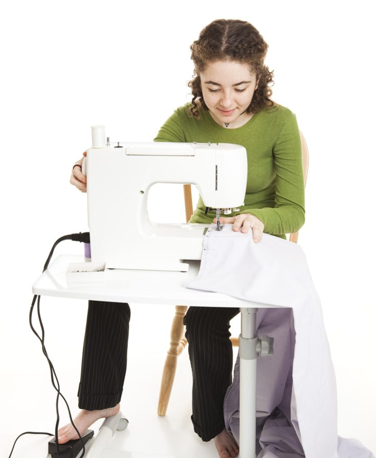 Teen girl using a sewing machine with a foot pedal. Full body isolated on white.
