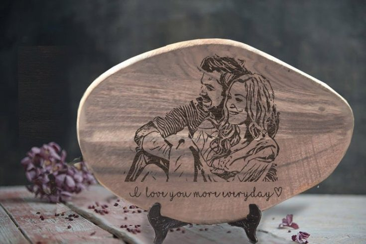 Artsy wood frame engraved by hand and couple's photograph though wood burning.