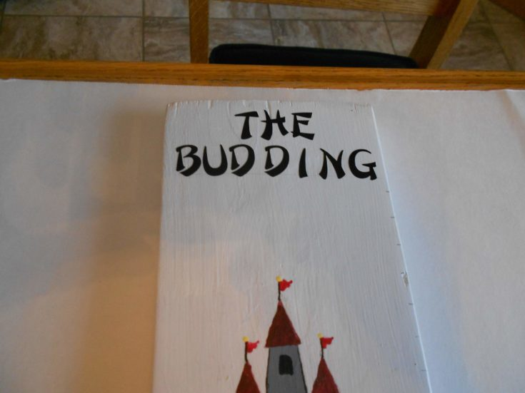 The Budding lettering on the a white painted board with a castle drawing below