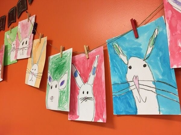 Watercolor bunny portrait painted by kids and hanged with clips on string.