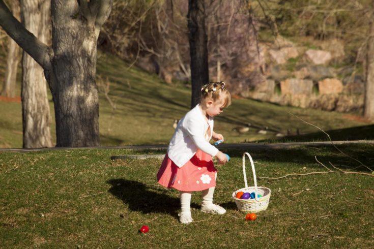 Little toddler girl on Easter egg hunt in urban park.