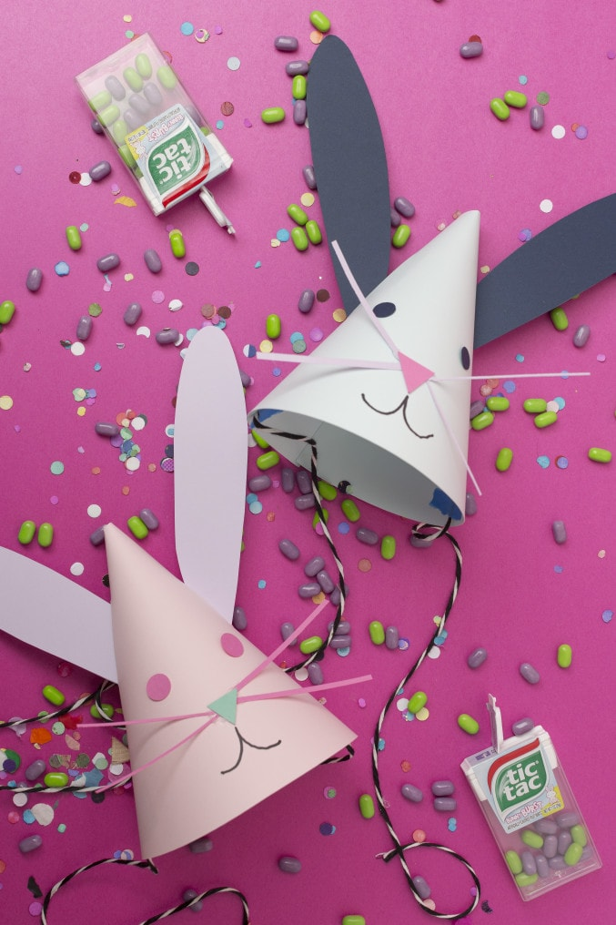 DIY Bunny design party hats with tictac candies spread on a pink background.