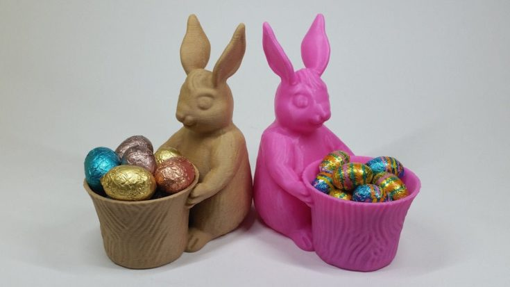 A brown and pink 3D printed rabbit planter with eggs inside.