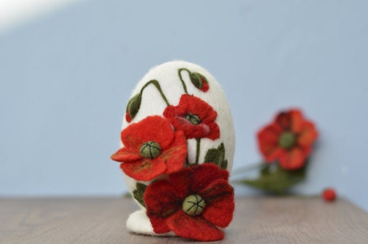 A felt easter egg craft design with red flowers on top of the table.