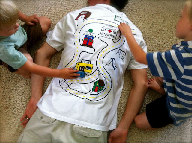 Dad lying on the floor wearing Car Shirt, with 2 boys playing with their car on his back