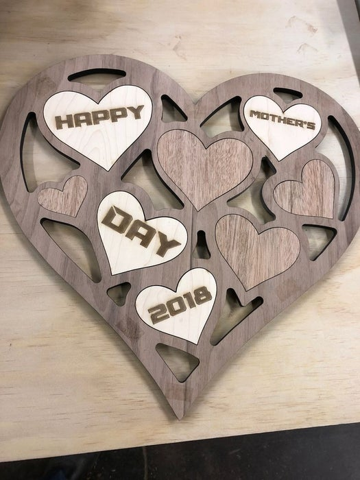 Personalized heart-shaped wooden art piece with a message.