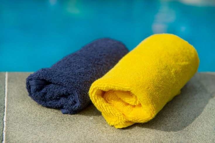 Towels in blue and yellow near the swimming pool