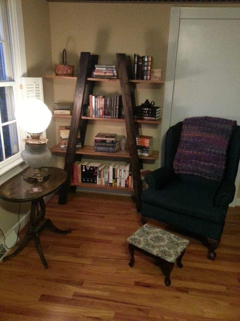 4 layers truss-shaped shelf besides a chair