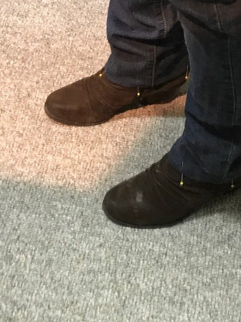 a cropped shot of the shoes and jeans with pin on it