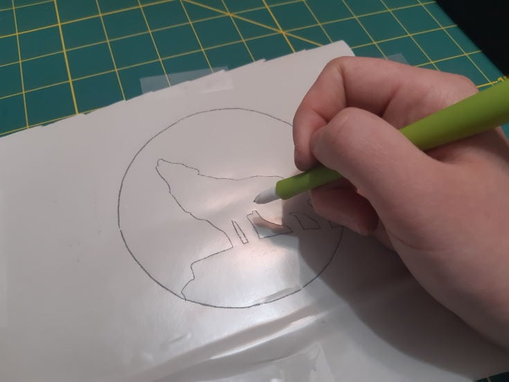 woman's hands draws on white paper