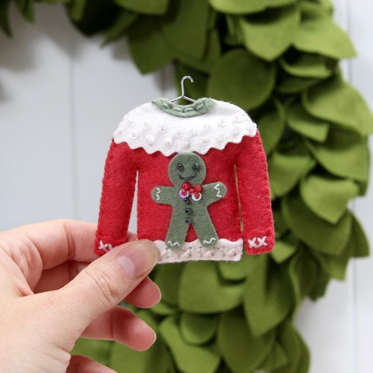 woman's hand holding ugly sweater