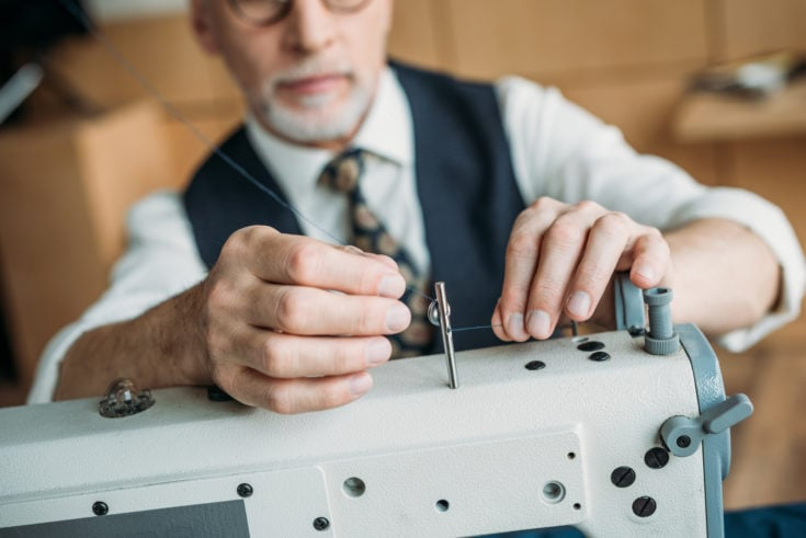 Cropped image of senior tailor threading needle of sewing machine at sewing workshop