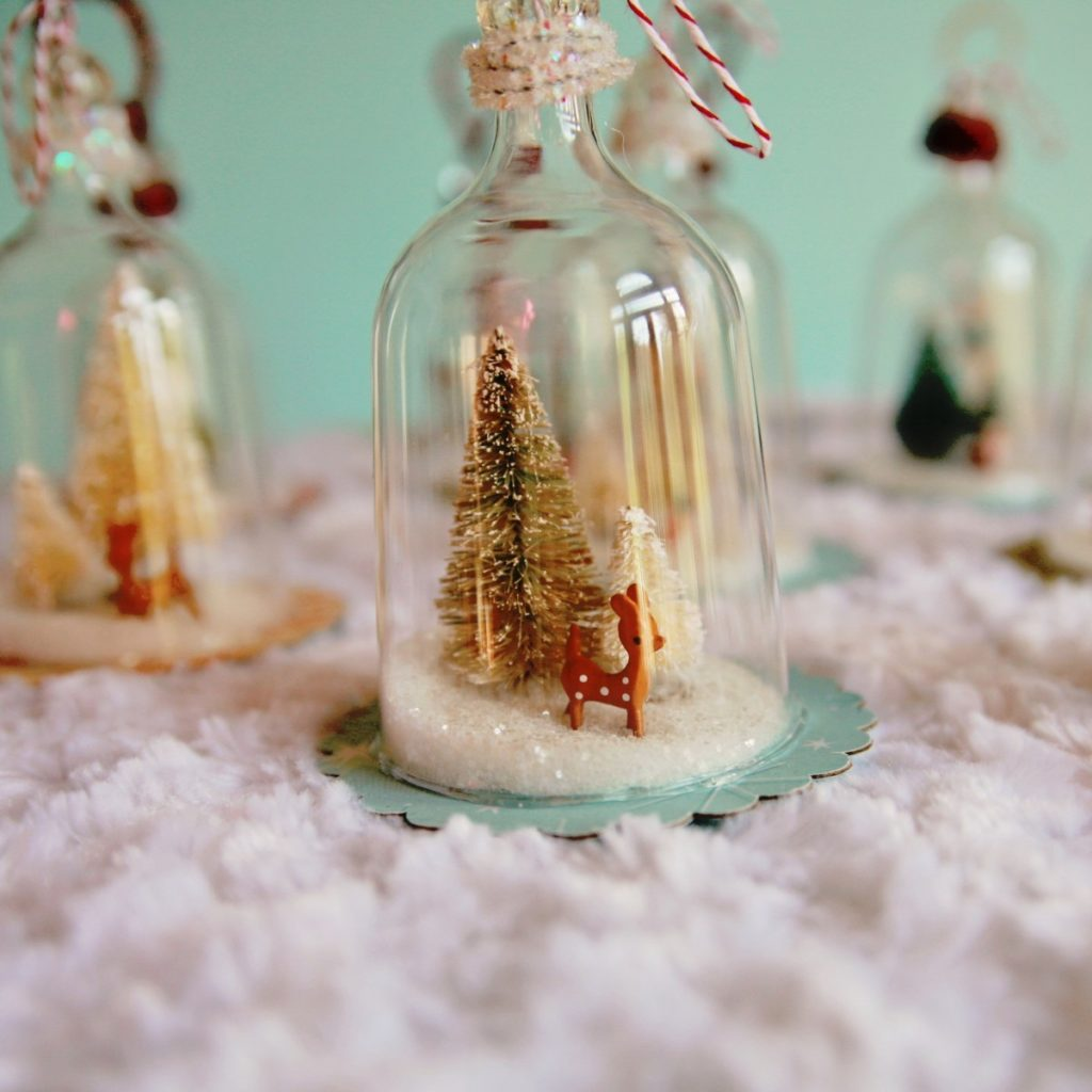 Clear glass bell ornament with Christmas tree and reindeer inside