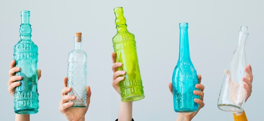 Different shapes and colors of empty wine lifted by hands.