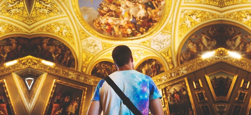 A closed shot of man looking on a paintings on wall and ceiling.
