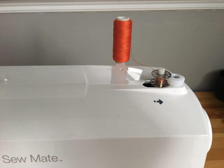 focus shot of orange thread and the top bobbin