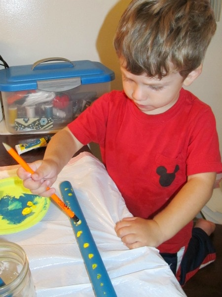 a boy in red shirt painting the blue wooden dowel