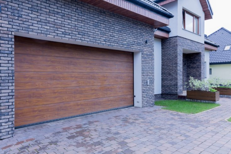 View of wooden garage door and main entrance of detached house