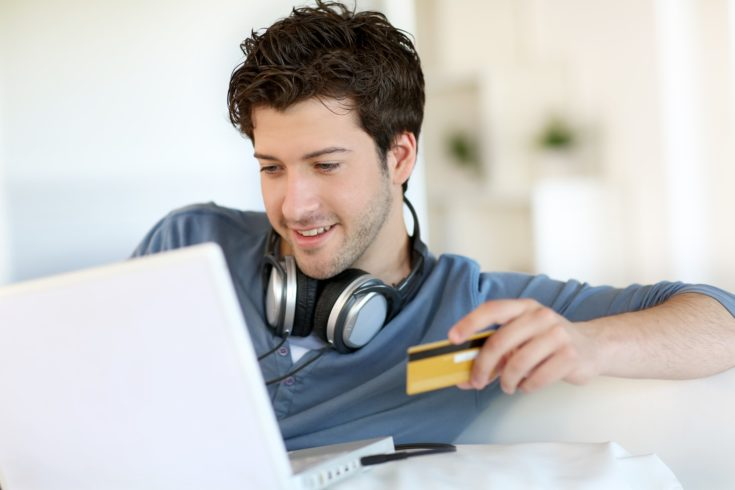 Young man looking for something to buy on internet with a laptop