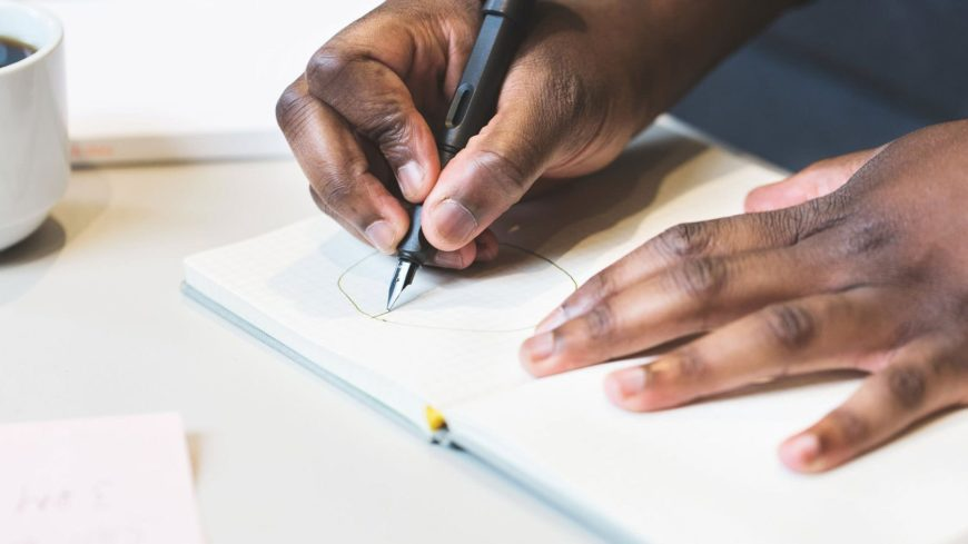 Black man's hand writing on notebook using fountain pen