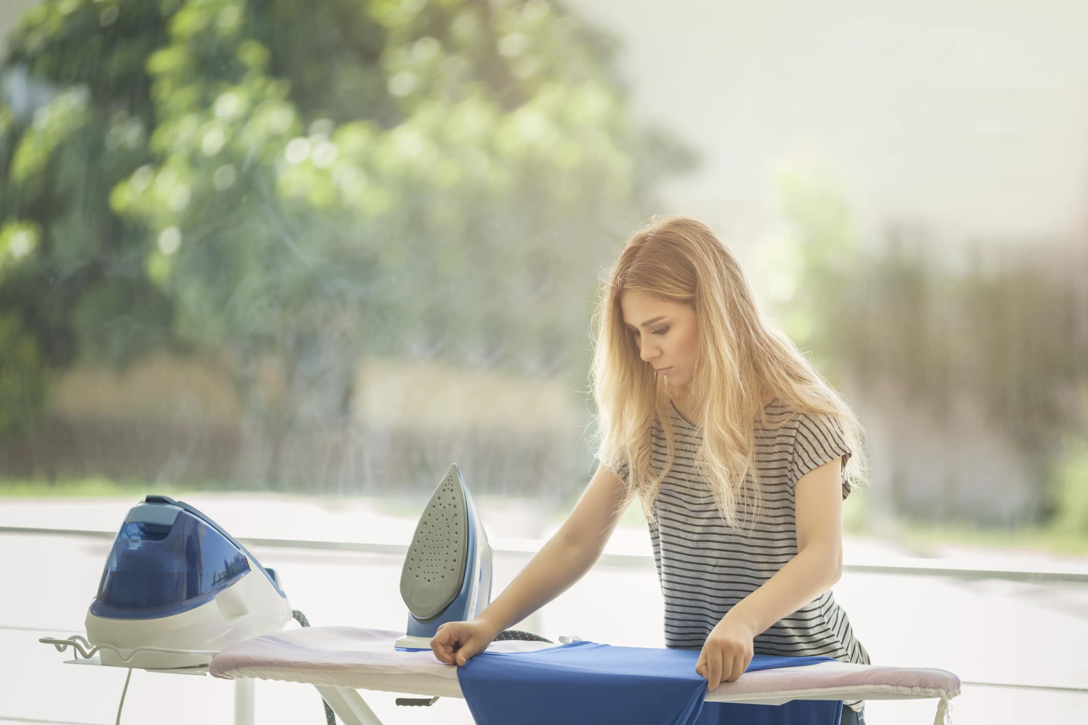 Woman ironing blue t-shirt on rack.