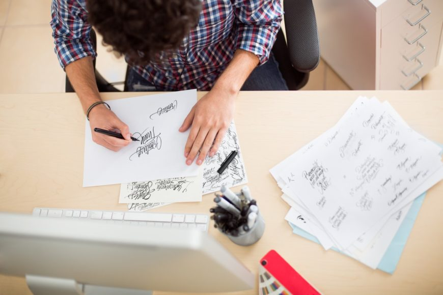 Man sitting down doing calligraphy on his office table