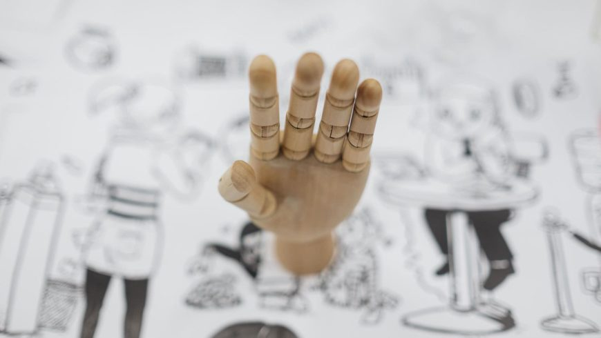 Wooden Mannequin hand in blurry drawing background