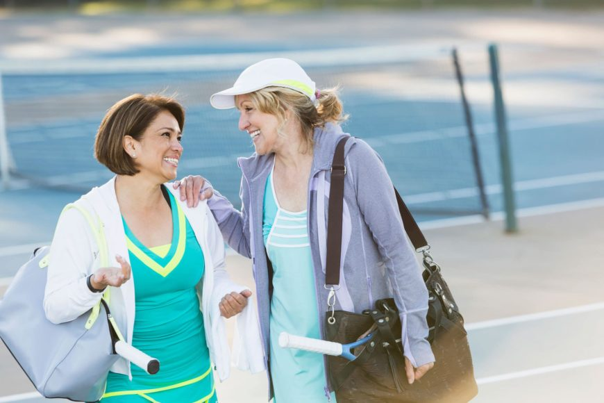 Two women in tennis attire with bags smiling each other