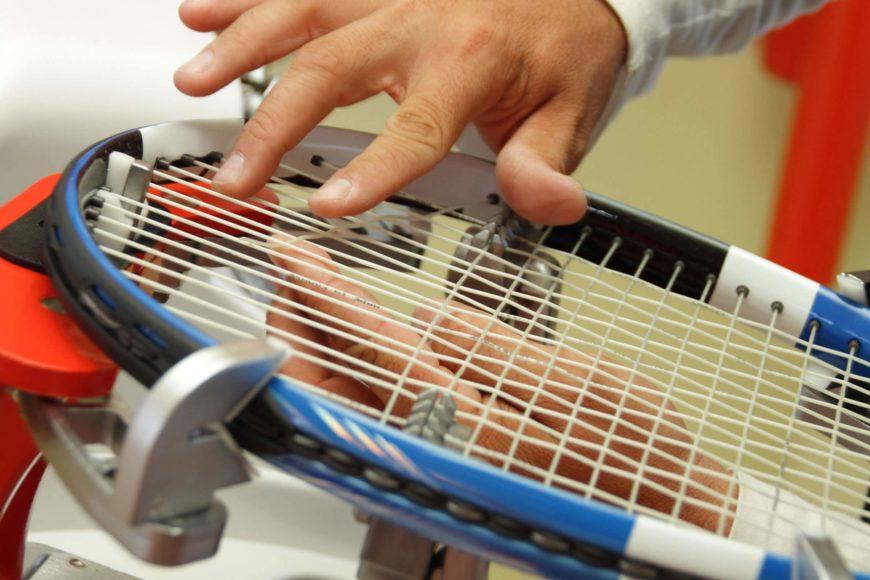Close up shot of tennis rocket and man's hand
