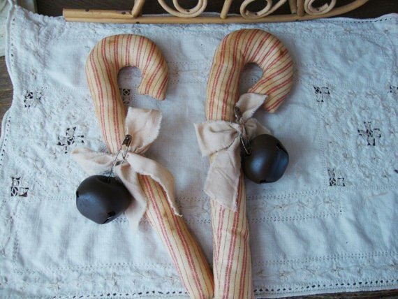 Cane wrapped in striped fabric with black bell on top of white cloth