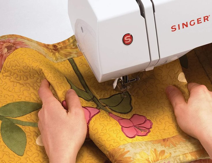 close up shot of a person's hand sewing a piece of cloth using singer sewing machine