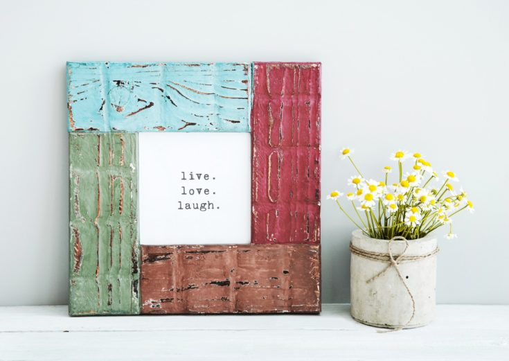 colored red, gree, blue frame LIVE, LOVE, LAUGH with chamomile in diy concrete pot. Skandinavian style room interior