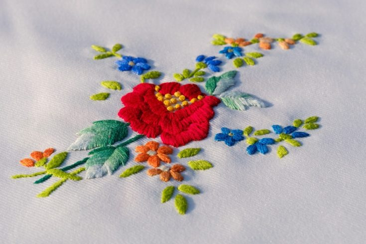 Embroidered flower on white cloth.