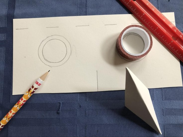 eyes cutouts on a mask with pencil and ruler