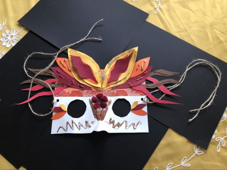 finished bird mask with black colored paper and colorful headdress