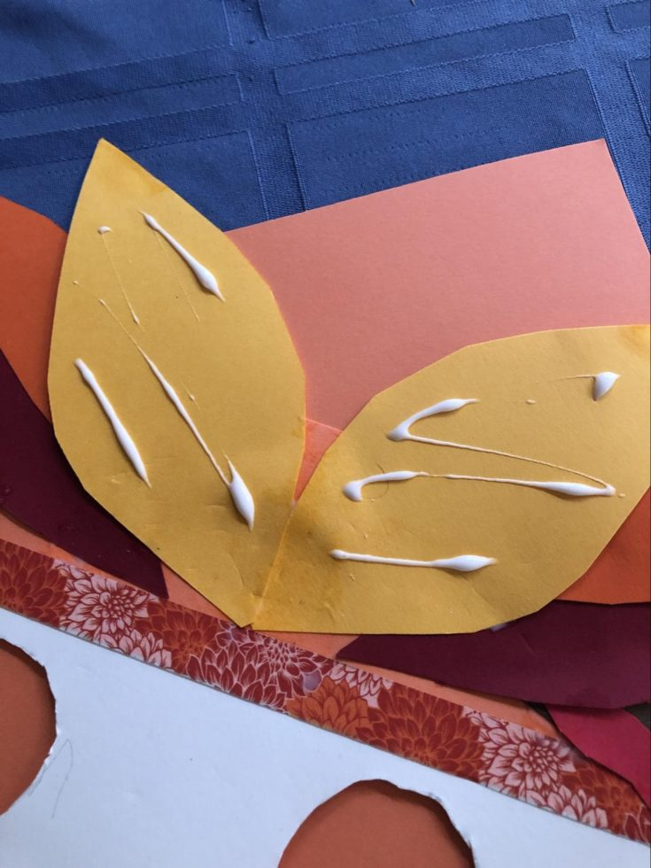 glue on the yellow feather cutout colored paper