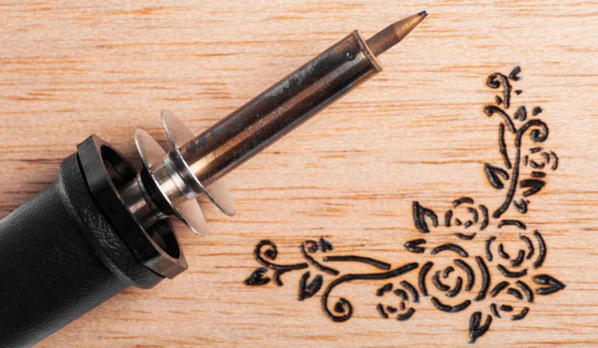 Wood burning tool in wooden background