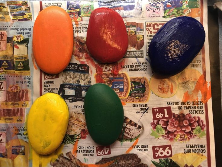 Smooth stones painted with red,blue,green,yellow and orange acrylic paint.