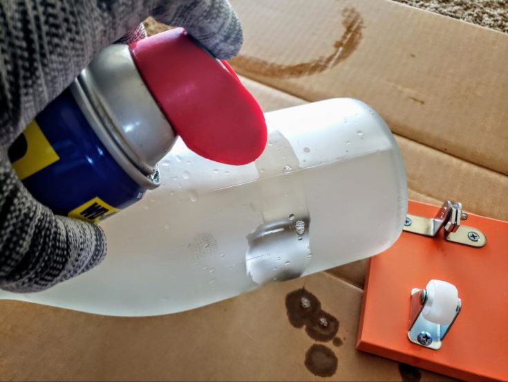 Close up shot of woman's hand spraying lubricant oil to the area of the bottle to score.