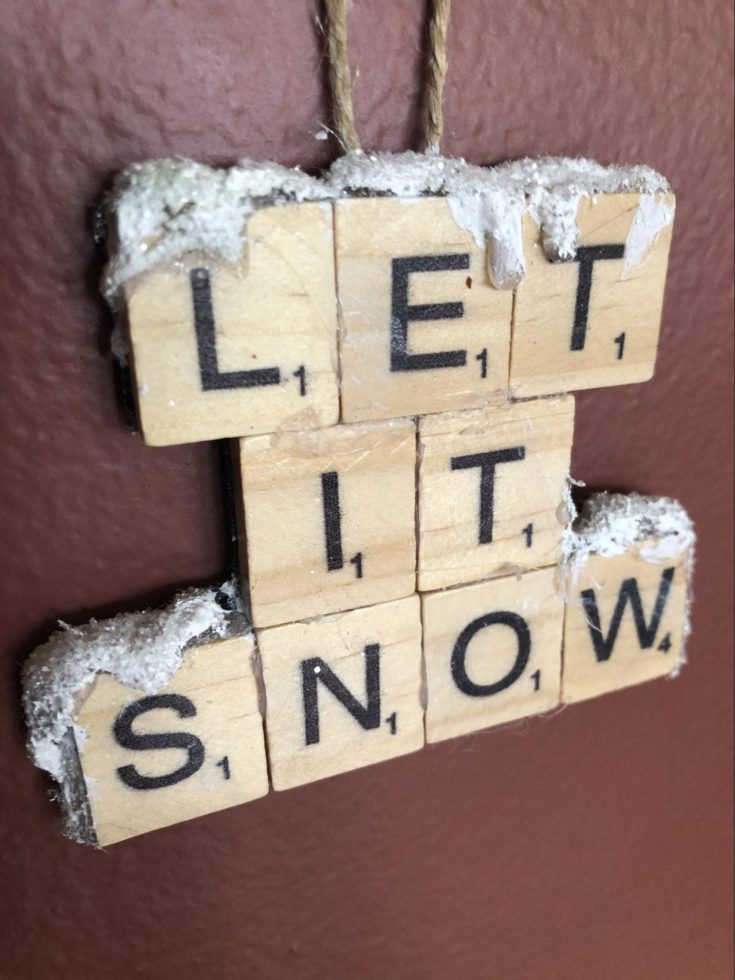 LET IT SNOW ornaments on a brown background.