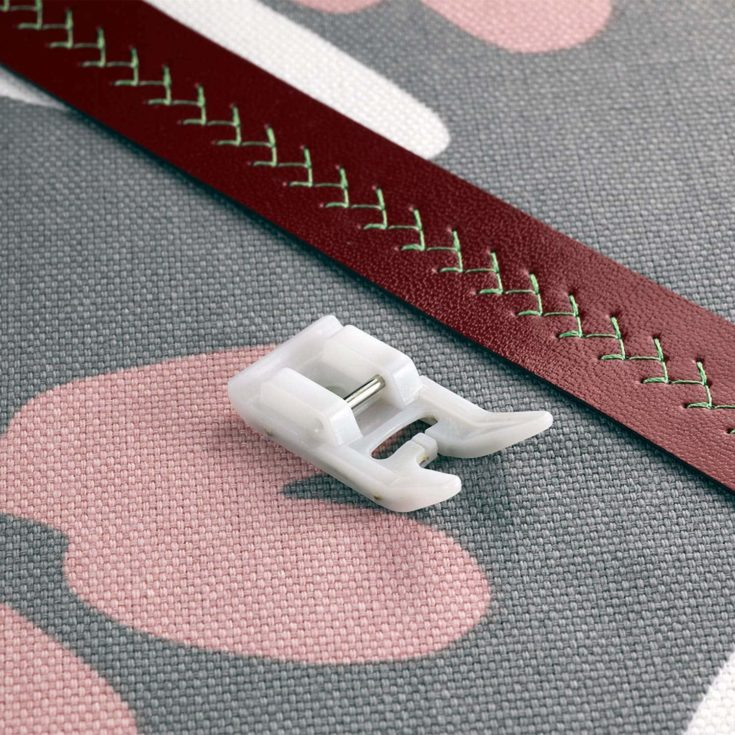 presser foot on a thick fabric and maroon leather with stitches