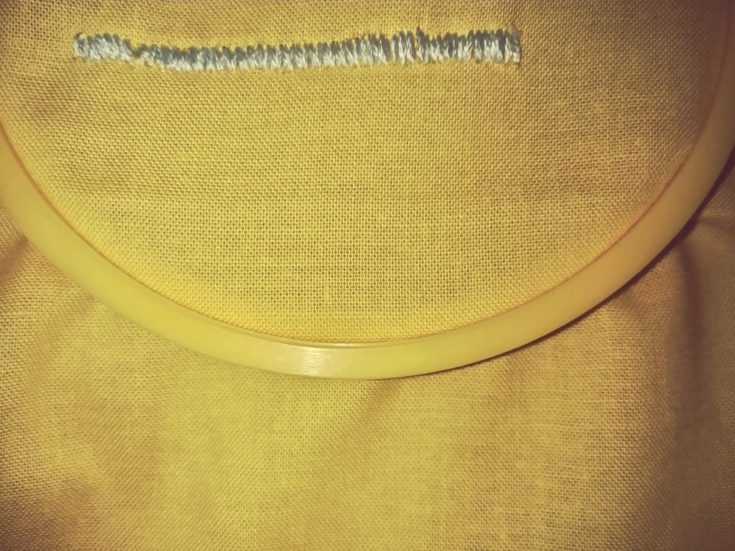 satin stitch embroidery example in a yellow cloth