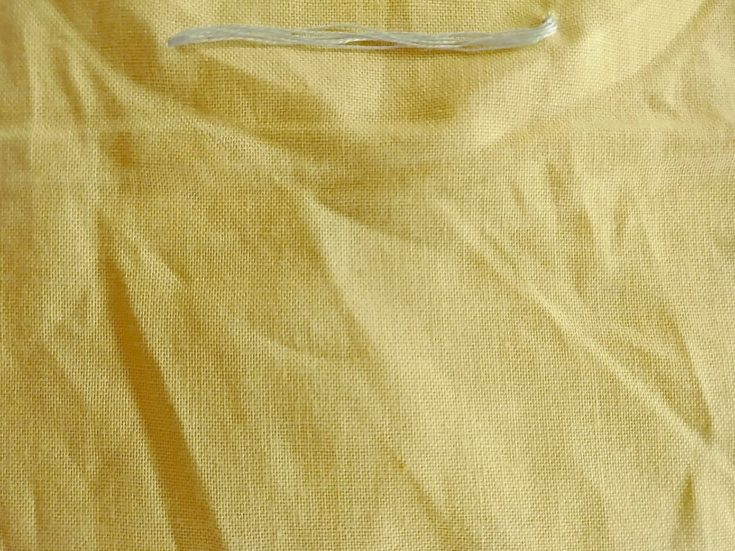 straight stitch embroidery example in a yellow cloth