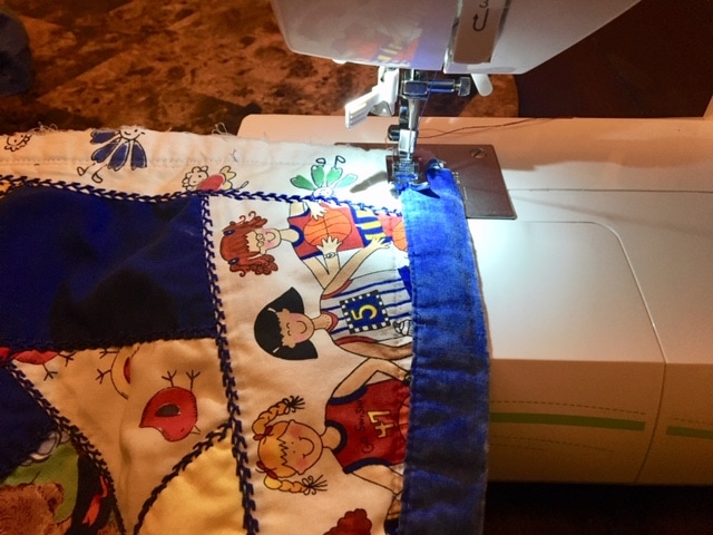 adding another strip of binding and sewing it on the edges of the cloth