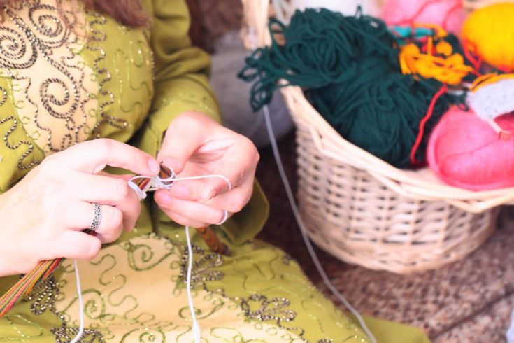 Close-up of woman hands knitting with stylish knitting needles