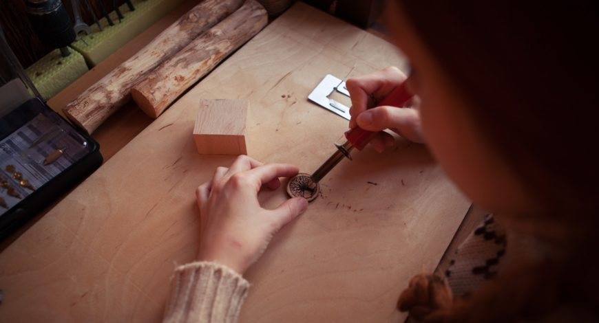 Girl doing wood burning on table with round small woods on her front