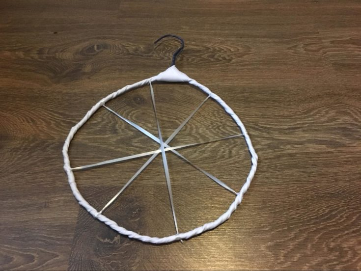wrapping the edges of the circular hanger with white ribbon